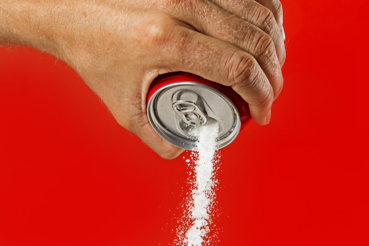 man hand holding refresh drink can pouring sugar stream in sweet and calories content of soda and energy drinks concept in unhealthy nutrition and diet concept